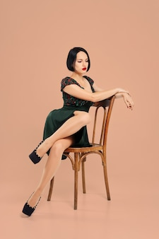 Menina bonita posando na cadeira no estúdio