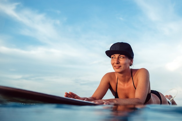 Menina bonita posando sentado em uma prancha de surf no oceano