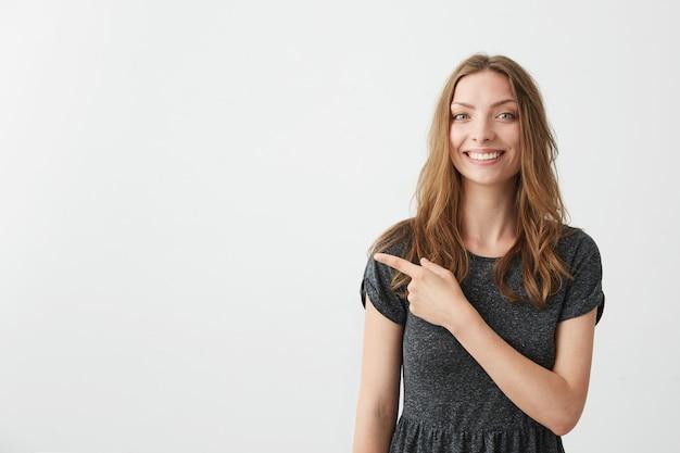Menina bonita positiva nova que sorri apontando o dedo no lado.