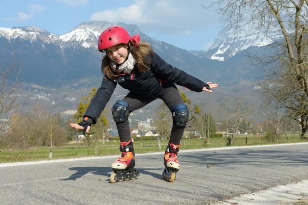 Menina bonita pré-adolescente de patins no capacete em uma pista