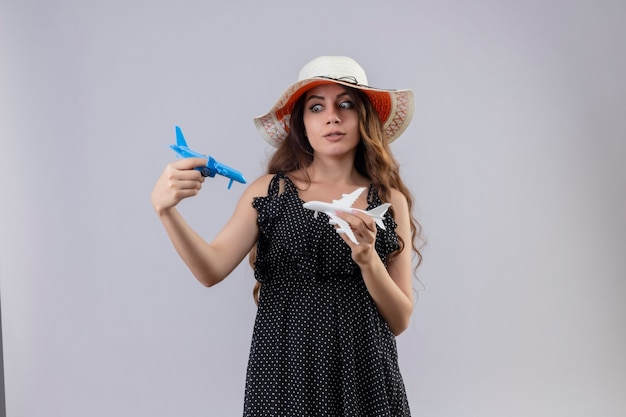 Menina bonita preocupada em um vestido de bolinhas com chapéu de verão segurando aviões de brinquedo brincando com eles em pé sobre um fundo branco