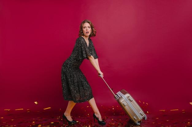Menina bonita preocupada em um vestido longo vintage arrastando uma grande mala