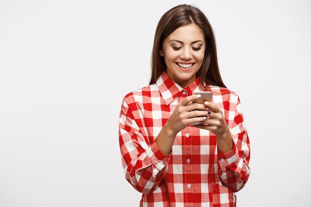 Menina bonita, preso no telefone, jogando jogos divertidos, se divertindo