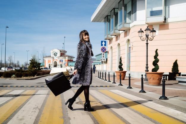 Menina bonita que anda através de uma passagem para pedestres em um casaco de pele com sacos de compras. bom dia de sol para fazer compras, estilo urbano de rua