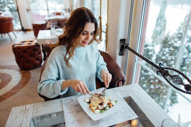 Menina bonita que come a salada de caesar no restaurante