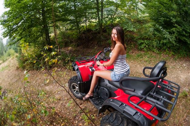 Menina bonita que conduz o atv de quatro rodas