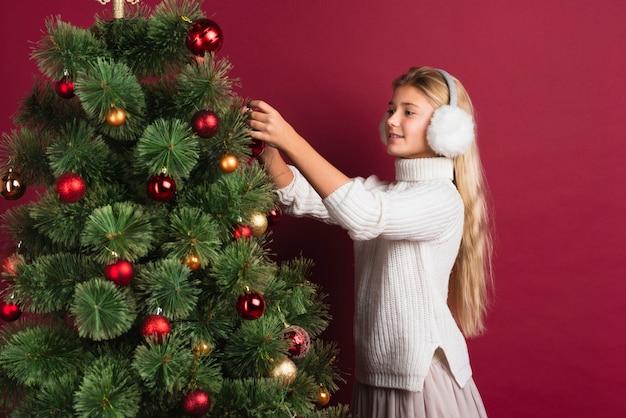 Menina bonita que decora a árvore de natal