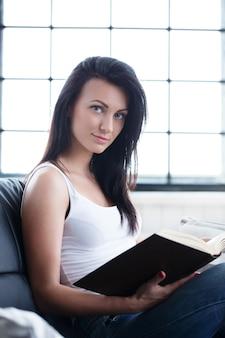 Menina bonita que estuda com um livro
