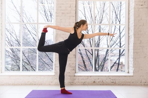 Menina bonita que faz o pose da ioga à posição direita no assoalho oposto à janela em um quarto brilhante.
