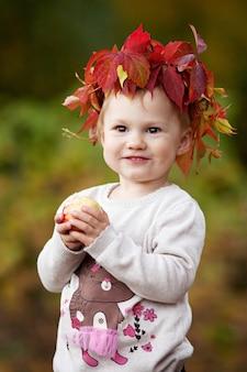 Menina bonita que guarda maçãs no jardim do outono. menina brincando com maçãs. diversão de halloween e ação de graças para a família.