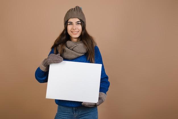 Menina bonita que guarda um quadro branco em suas mãos em um fundo do braun no estúdio.