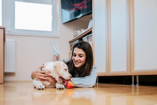 Menina bonita que joga com filhote de cachorro bonito em casa.