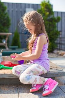 Menina bonita que joga na caixa de areia com brinquedos no quintal