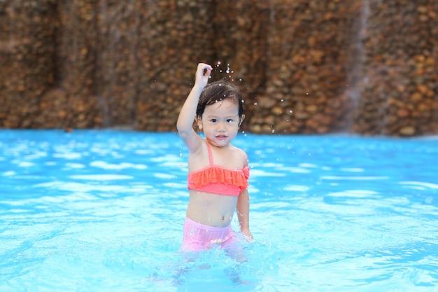 Menina bonita que joga na piscina ao ar livre