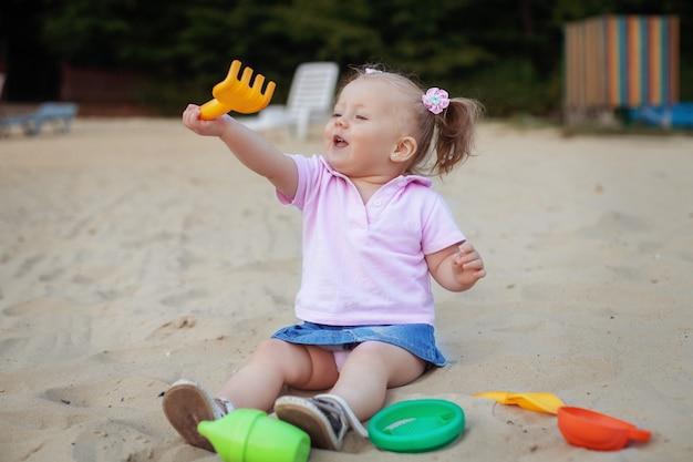 Menina bonita que joga no ancinho da caixa de areia. o conceito de infância e desenvolvimento.