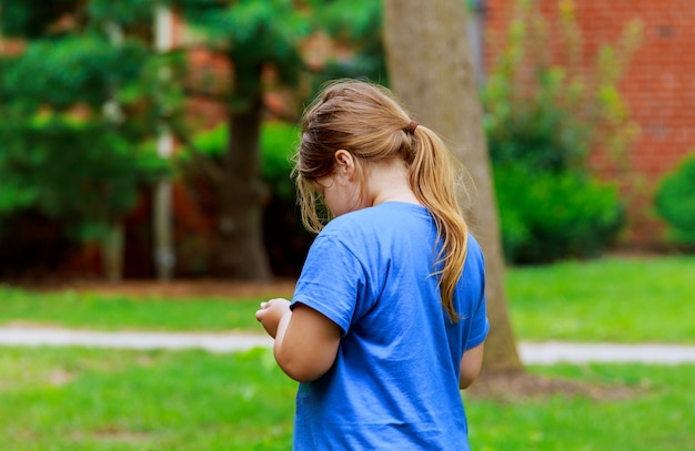 Menina bonita que joga no telefone na rua