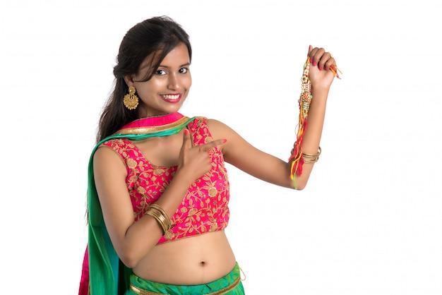 Menina bonita que mostra rakhi por ocasião de raksha bandhan em um fundo branco. a irmã amarra rakhi como símbolo de intenso amor por seu irmão.