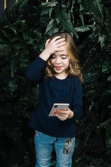 Menina bonita que olha o telefone esperto que põe a mão sobre sua cabeça