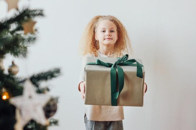 Menina bonita que prende a caixa de presente grande, tempo do natal