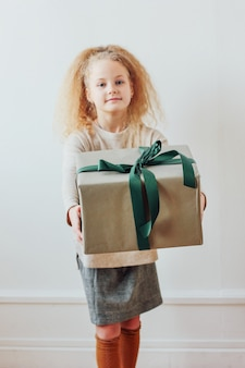 Menina bonita que prende a caixa de presente grande