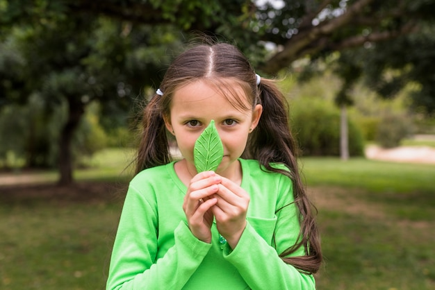 Menina bonita que prende a folha verde artificial na frente de seu nariz
