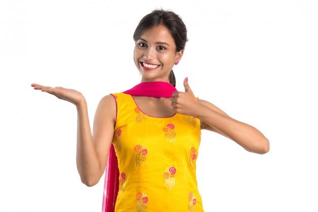 Menina bonita que prende e que apresenta algo na mão com sorriso feliz.