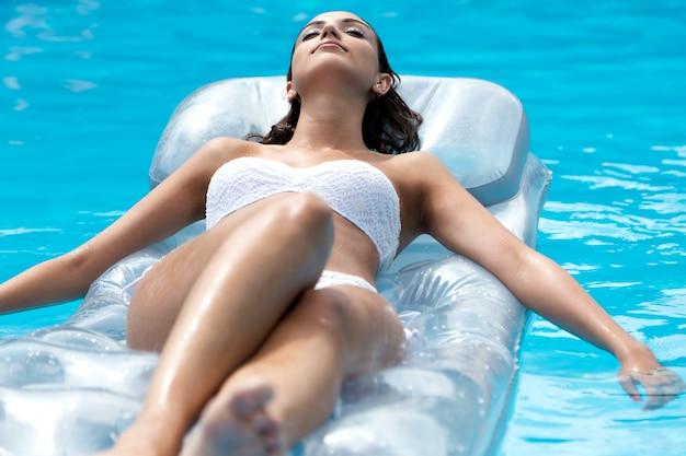Menina bonita que relaxa na piscina no verão
