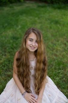 Menina bonita que senta e que sorri fora durante o dia.