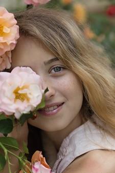 Menina bonita que senta e que sorri perto das flores, fora durante o dia.