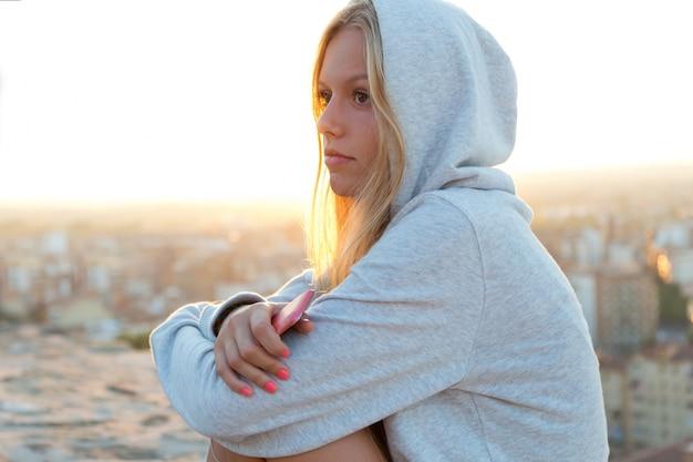 Menina bonita que senta-se no telhado e que escuta a música.