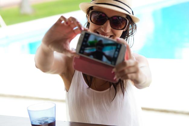 Menina bonita que toma um selfie na piscina.