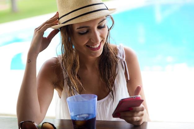 Menina bonita que toma um telefone móvel na piscina.