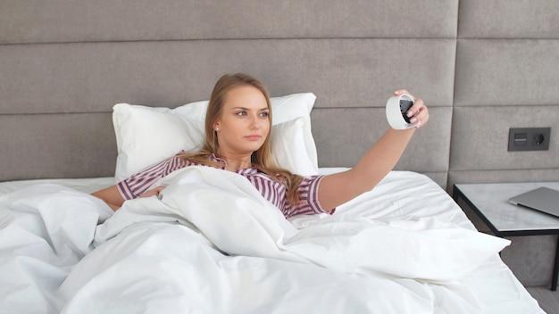 Menina bonita quer relaxar e dormir, a menina define um despertador para não dormir demais