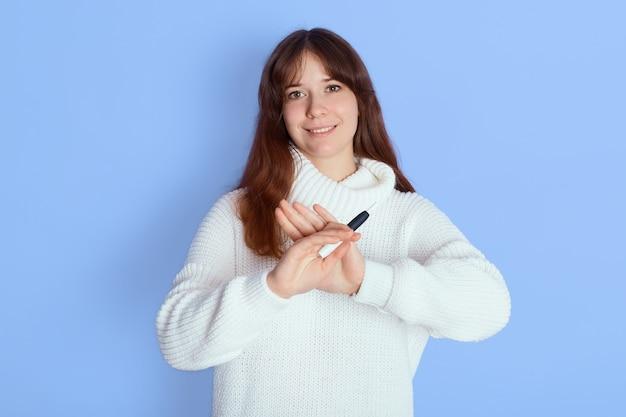 Menina bonita recusa cigarro eletrônico, mostrando gesto de parada com as palmas das mãos