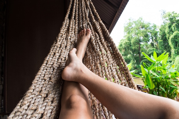 Menina bonita, relaxando em uma rede em casa