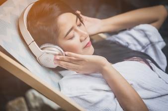 Menina bonita relaxante conceito de beleza. sorriso feliz da menina anf ouvir música com auscultadores