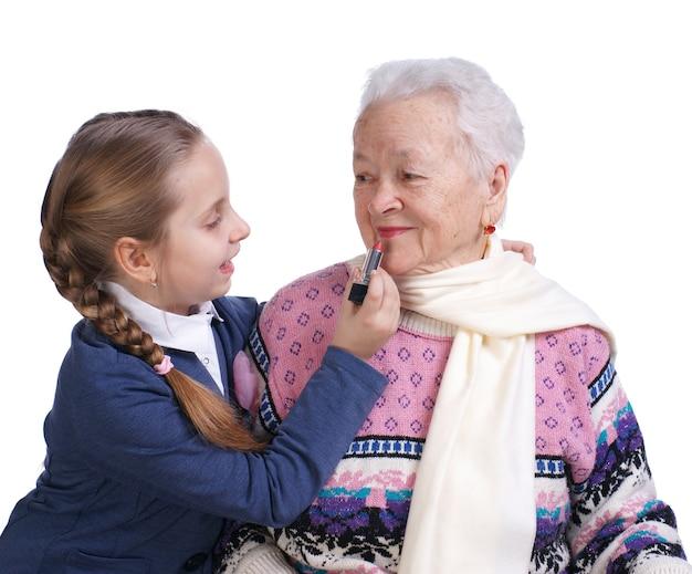 Menina bonita rouging lábios da avó em um fundo branco
