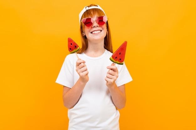 Menina bonita ruiva em uma camiseta branca em uma parede laranja, maquete, retrato emocional
