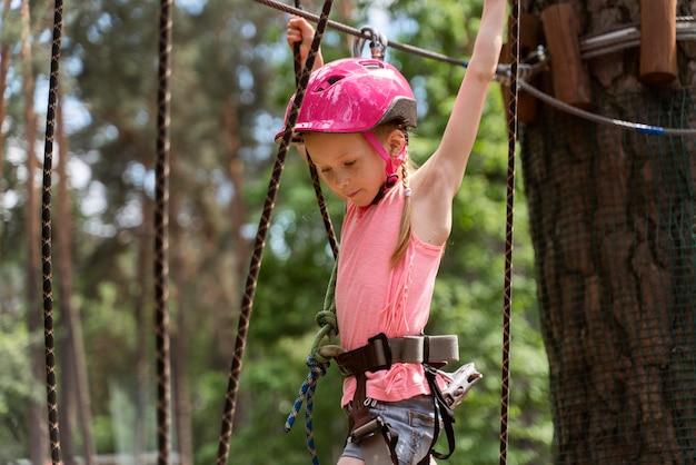Menina bonita se divertindo em um parque de aventura Foto gratuita