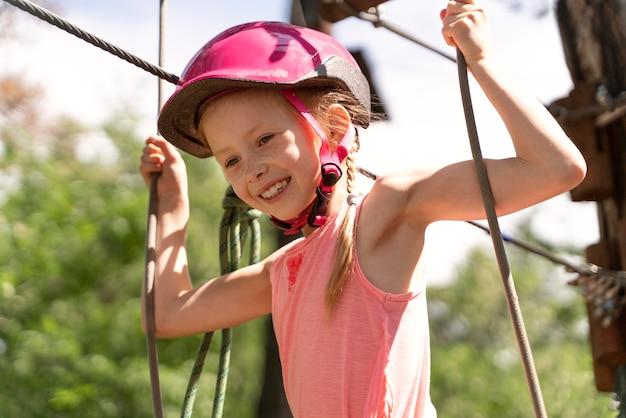 Menina bonita se divertindo em um parque de aventura