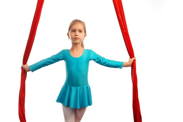 Menina bonita se preparando para o desempenho em arejadas fitas vermelhas em um fundo branco. conceito de acrobacia e bom alongamento para crianças. lugar de publicidade