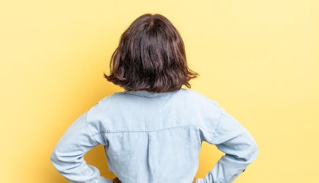 Menina bonita se sentindo confusa ou cheia ou dúvidas e perguntas, imaginando, com as mãos nos quadris, vista traseira