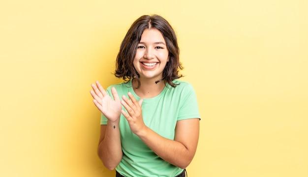 Menina bonita se sentindo feliz e bem-sucedida, sorrindo e batendo palmas, dizendo parabéns com um aplauso
