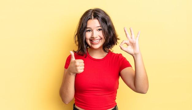 Menina bonita se sentindo feliz, maravilhada, satisfeita e surpresa, mostrando gestos de ok e polegar para cima, sorrindo
