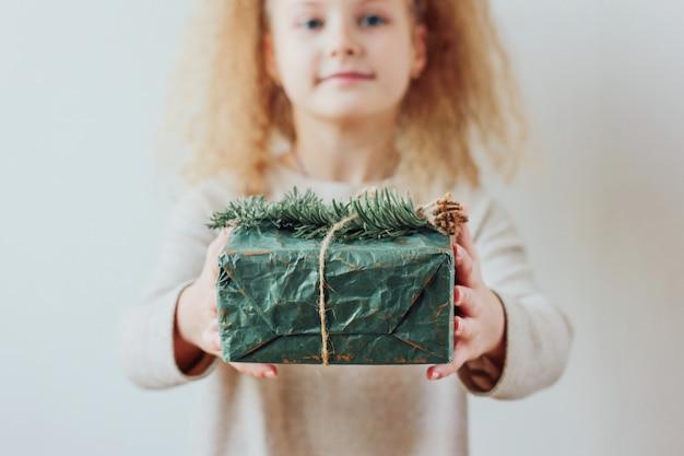 Menina bonita segurando a caixa de presente, tempo de natal