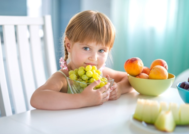 Menina bonita, segurando a tigela com uvas na mesa