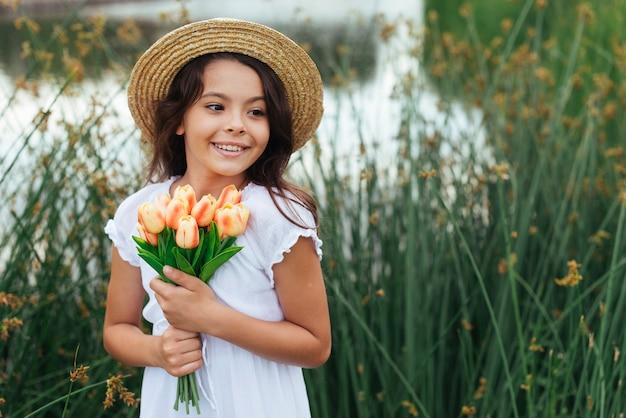 Menina bonita segurando flores à beira do lago