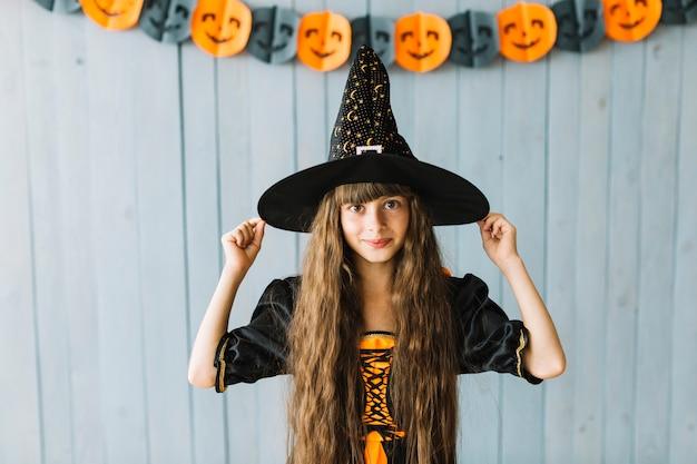 Menina bonita segurando no chapéu de bruxa e sorrindo para a festa de halloween