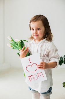 Menina bonita segurando o cartão com eu amo a inscrição de mãe