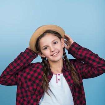 Menina bonita segurando o chapéu na cabeça